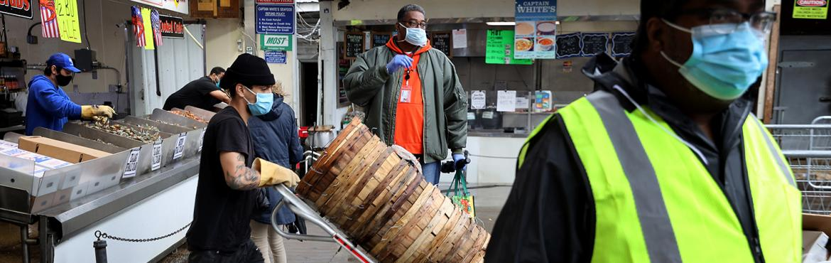 Employees, customers and security guards maintain social distancing at DC Wharf's Fish Market