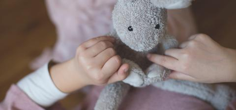 Child holding stuffed animal
